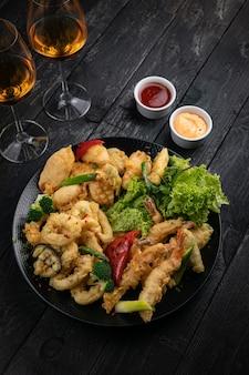 블랙 테이블에 소스와 화이트 와인을 곁들인 구운 해산물 모듬