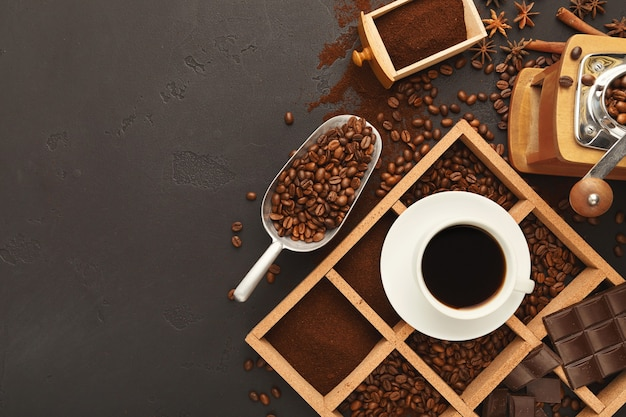 Ассорти из молотого кофе и жареных зерен в деревянной квадратной рамке на сером текстурированном сланце. вид сверху на чашку с напитком и старинной мясорубкой, копией пространства. шаблон для предупреждения кафе или кофейни