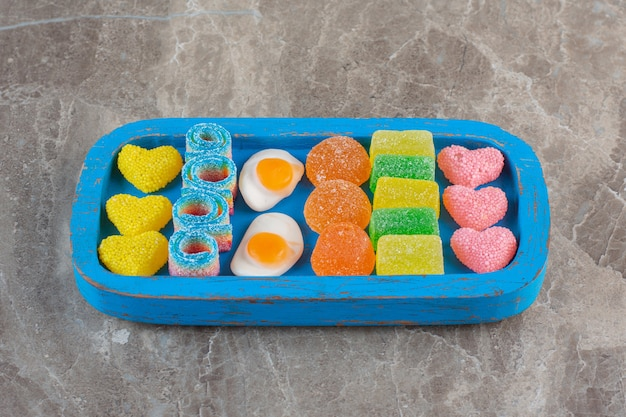 Assorted gummy candies on blue wooden plate over grey surface.