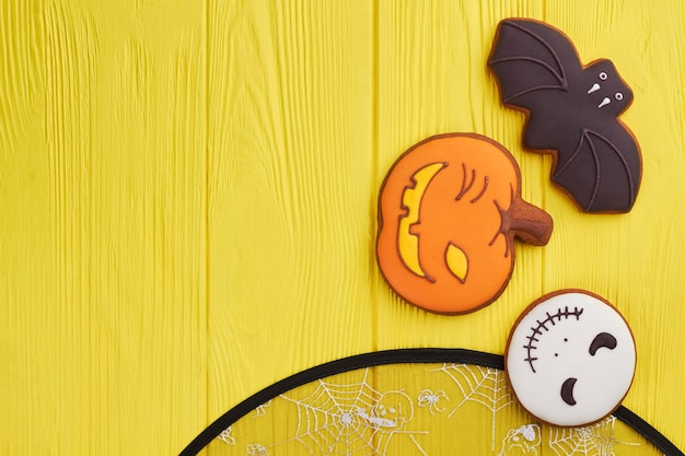 Assorted hallowen cookies on yellow background halloween holiday sugar biscuits including pumpkin ba...