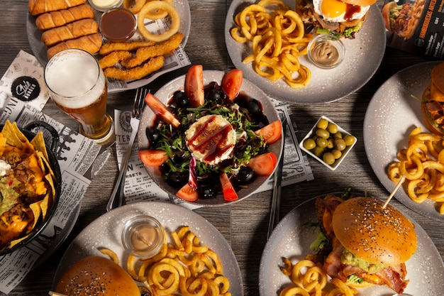Assorted hamburger dishes and tapas on wooden table seen from above. isolated image.