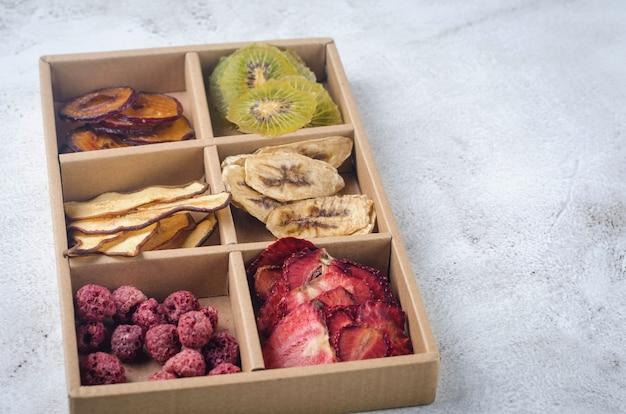 灰色の背景のボックスに手作りのドライチップスの詰め合わせ。健康的な食事のコンセプト、スナック、砂糖なし。ケアパッケージ、季節のギフトボックスを準備しています。感謝祭、クリスマス、
