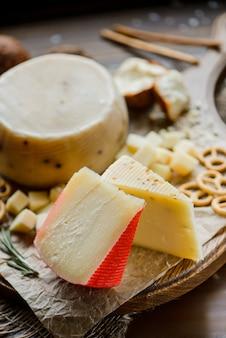 Ассорти твердых сыров с кренделями на разделочной доске. на деревянном фоне. выборочный фокус.