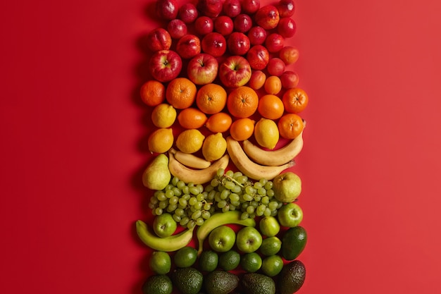 Agrumi sani assortiti su sfondo rosso brillante. pesche mature, mele, arance, banane, uva e avocado per una sana alimentazione. set di cibo nutriente. dieta equilibrata, alimentazione pulita.