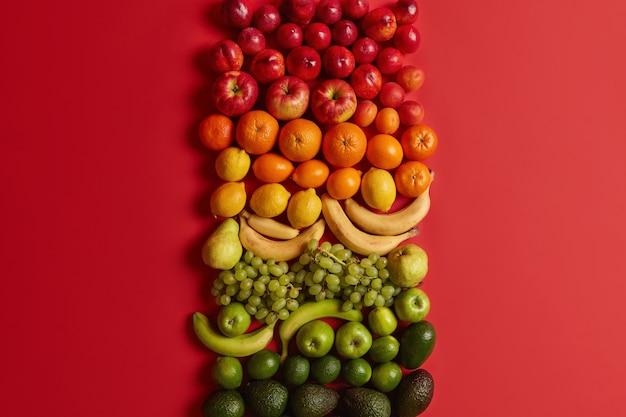 밝은 빨간색 배경에 모듬 된 건강한 감귤류. 건강한 영양을 위해 잘 익은 복숭아, 사과, 오렌지, 바나나, 포도, 아보카도. 영양가있는 음식 세트. 균형 잡힌 식단, 깨끗한 식사.