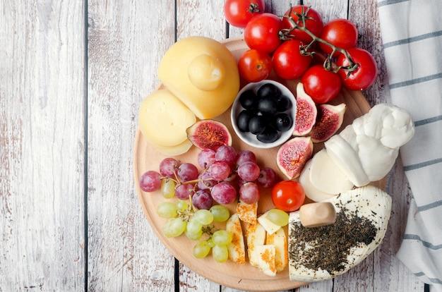 모듬 수제 치즈 파스타 필라 타, 나무 배경에 다양한 모양과 크기의 프로 볼 로네, 술루 구니, 피그 테일, caciocavallo, 할루 미, 토마토 후추, 올리브, 포도, 무화과 및 허브