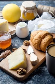 Ассорти из домашних сыров с медом, фруктами, печеньем и орехами на столе. свежие молочные продукты, здоровые органические продукты. вкусная закуска.