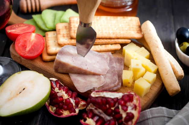 테이블에 꿀, 과일, 쿠키, 견과류와 모듬 수제 조각 치즈. 신선한 유제품, 건강한 유기농 식품. 맛있는 전채.