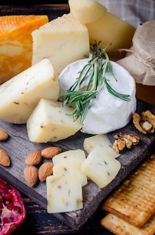 テーブルの上に蜂蜜、フルーツ、クッキー、ナッツを添えた自家製チーズの盛り合わせ。新鮮な乳製品、健康的な有機食品。美味しい前菜。