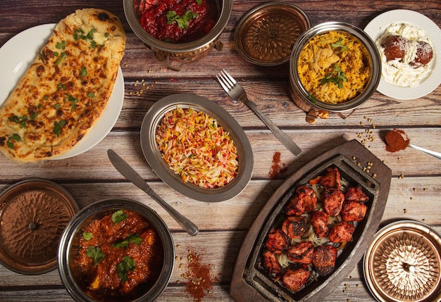 Assorted indian dishes of rice and curry on wooden wall. top view