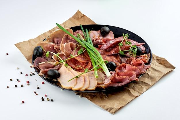모듬 이탈리아 고기 별미-햄, 로스트 비프, 살라미 소시지, 프로슈토, 초리 조가 어두운 표면에 베이지 색 접시에 담겨 있습니다.
