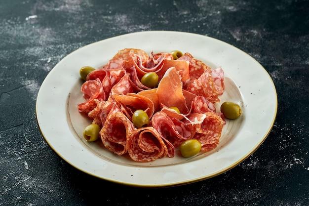 모듬 이탈리아 고기 별미-어두운 표면에 베이지 색 접시에 살라미 소시지, 프로슈토, 초리 조