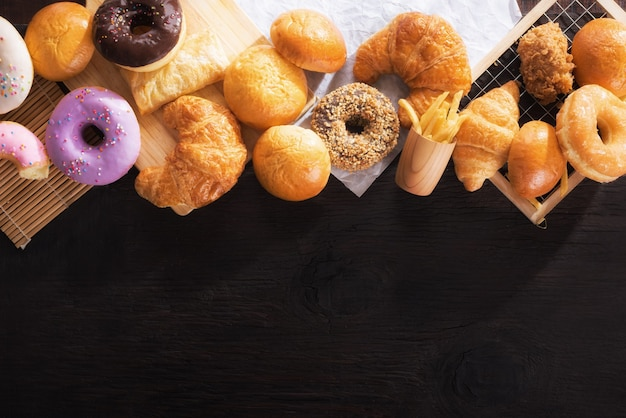 Assorted junk food multiple type on black wooden table of top view with copy space.