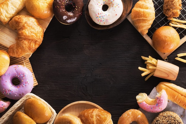 Assorted junk food multiple type on black wooden table of top view with copy space. Premium Photo