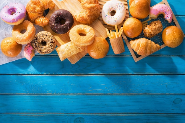 Assorted junk food multiple type on blue wooden table of top view with copy space.
