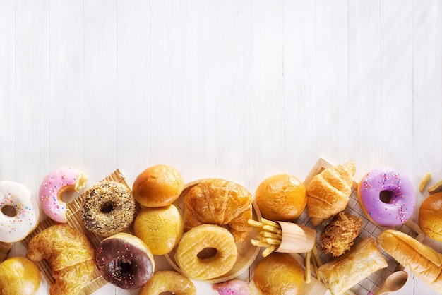 Assorted junk food multiple type on white wooden table of top view with copy space.