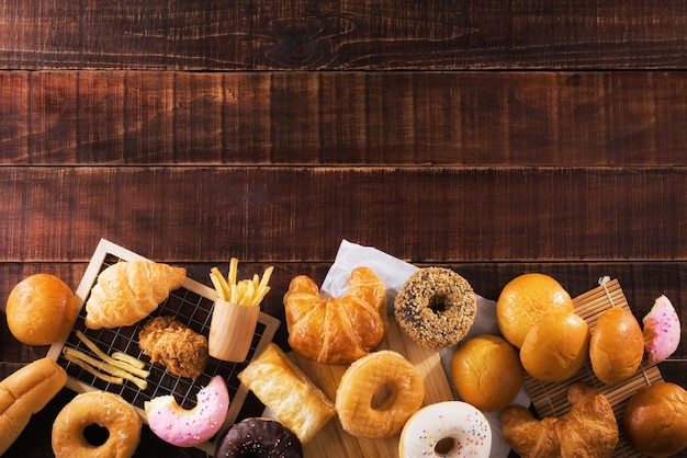 Assorted junk food multiple type on wooden table of top view with copy space.