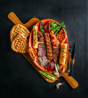 Assorted kebabs with vegetables and flat bread on huge wooden board