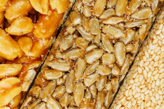 Assorted kozinaki, sweets from sunflower seeds, sesame and peanuts filled with brilliant glaze. macro