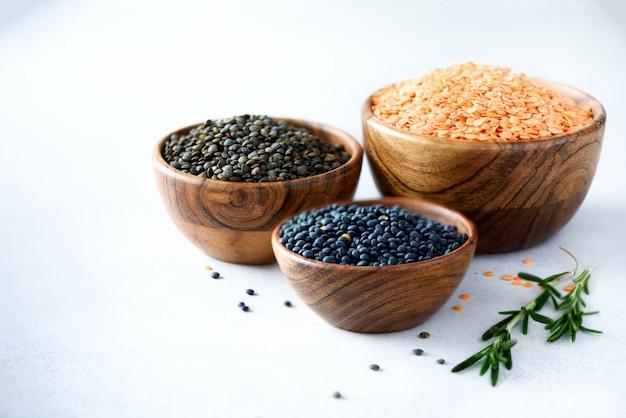 レンズ豆の盛り合わせ。グレーのコンクリートにローズマリーと木製のボウルに大理石、赤と黒の生有機レンズ豆。コピースペース