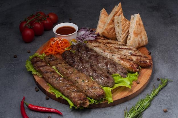 Assorted lula kebab: pork, lamb, chicken on a wooden board