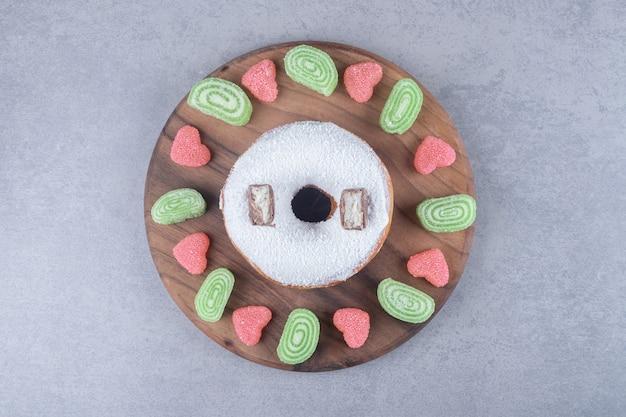 Мармелады в ассортименте, окружающие большой пончик на деревянной доске на мраморной поверхности