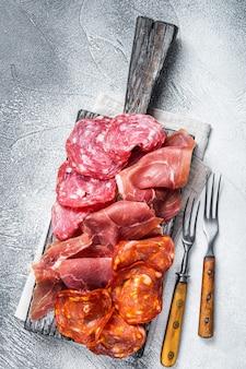 Ассорти мясных закусок - салями, хамон, колбаски чорисо. белый стол. вид сверху.