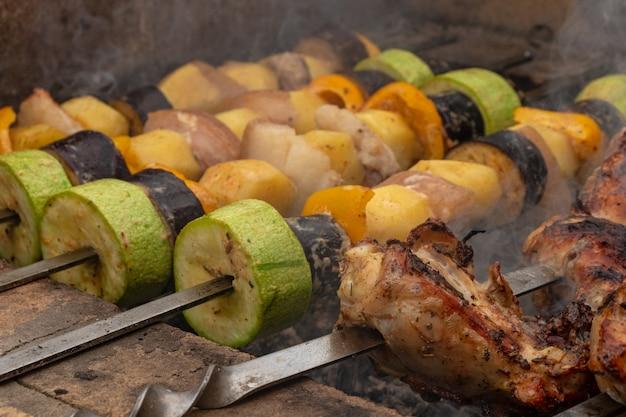 여름 가족 저녁 식사를 위해 구운 바베큐 그릴에 닭고기, 돼지고기 및 다양한 야채로 만든 모듬 고기