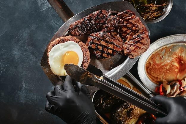 Мясное ассорти на гриле готовить руками в перчатках, разложить на тарелке, овощи и специи, на кухонном столе при подаче мяса, с разложенными салфетками и ножами.