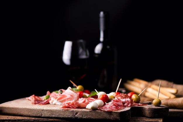 다양한 고기와 체리 모짜렐라 치즈, 배경에 와인 한 병과 유리가 있는 나무 커팅 보드에. 이탈리아식 전채