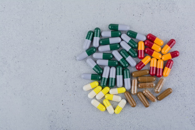 Assorted medical capsules on marble surface.