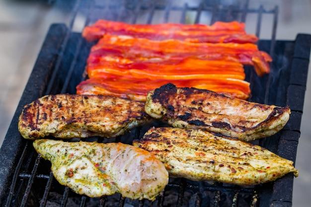 鶏肉と豚肉のミックスグリルの盛り合わせ、夏の家族の夕食のために調理されたバーベキューグリッドでローストしたソーセージ。