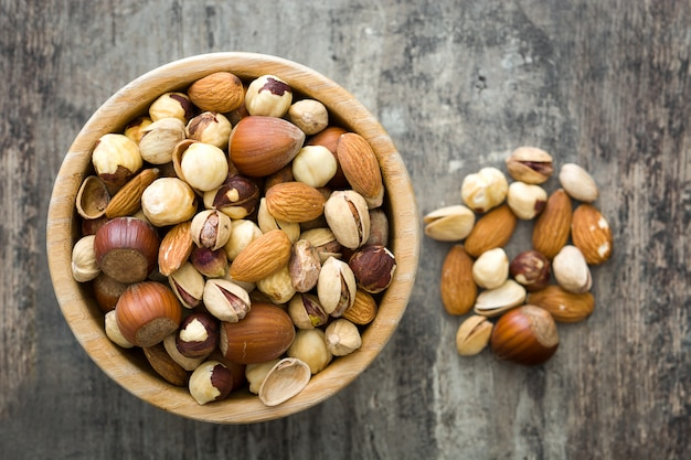 Assorted mixed nuts in bowl on wooden table top view