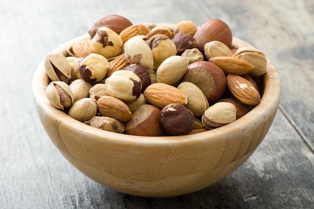 Ассорти из смешанных орехов в миску на деревянный стол