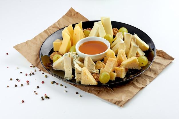 Ассорти аппетитных сыров: дорблю, пармезан, мягкие сыры, подается в черной тарелке с виноградом и медом.