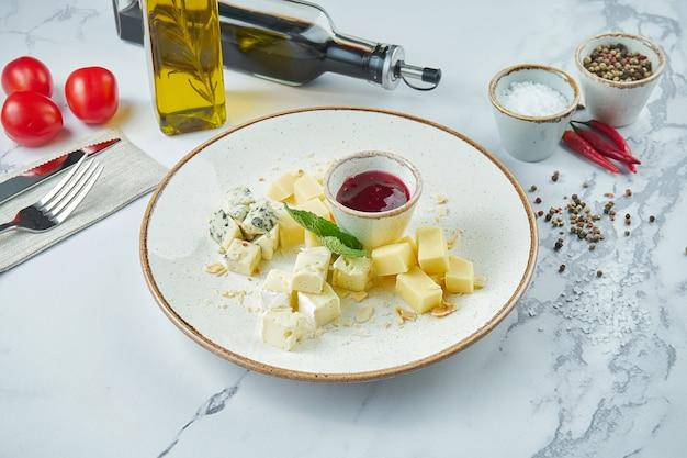 Ассорти аппетитных сыров: дорблю, пармезан, мягкие сыры, подается в белой тарелке с виноградом и медом.