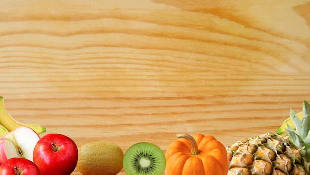 Assorted multi-color fresh ripe fruits on wooden background