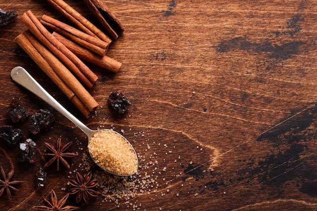 Ассорти из натуральной корицы, тростникового коричневого сахара, молотого кофе, ингредиентов для выпечки звездочек аниса на деревенском коричневом столе.