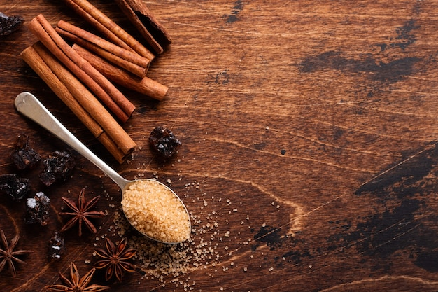 Assorted natural cinnamon, cane brown sugar, ground coffee, anise stars baking ingredients on a rustic brown table.