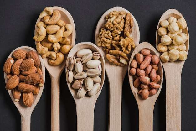 Assorted nice nuts in wooden spoons