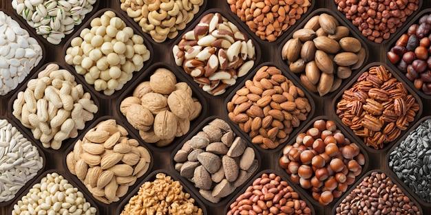 ナッツの盛り合わせの背景、大きなミックスシード。ローフード製品:ペカン、ヘーゼルナッツ、クルミ、ピスタチオ、アーモンド、マカダミア、カシュー、ピーナッツ、その他