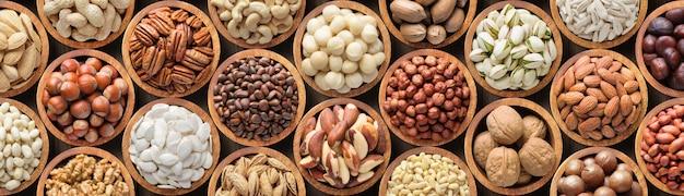 Ассорти орехов фон, вегетарианская еда в деревянных мисках, вид сверху