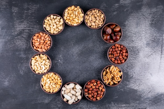 Assorted nuts and dried fruits in a cycle shaped mini different bowls with pecan, pistachios, almond, peanut, flat lay
