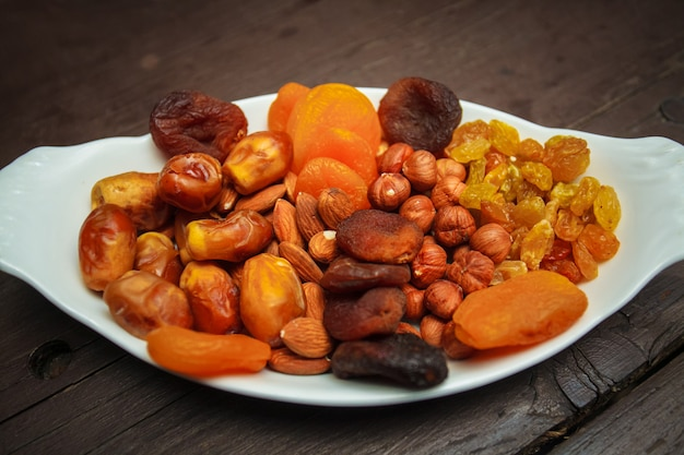 Assorted nuts and dried fruits in white plate.