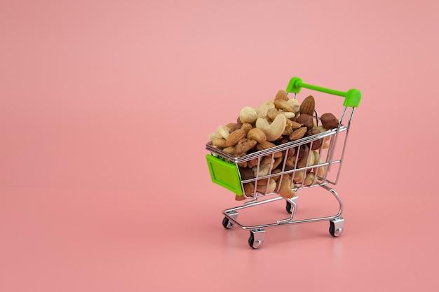분홍색 배경에 있는 sepermarket 바구니에 있는 여러 견과류