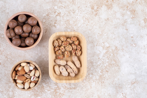 Ассорти из орехов в мисках рядом с миской шоколадных шариков