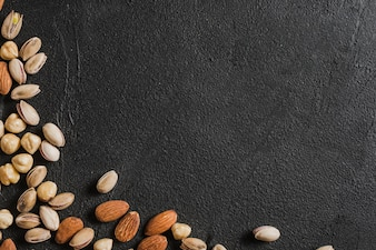 Assorted nuts on black plaster background
