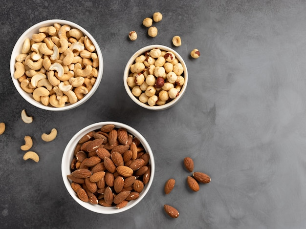 Assorted nuts in white bowls on a gray concrete wall