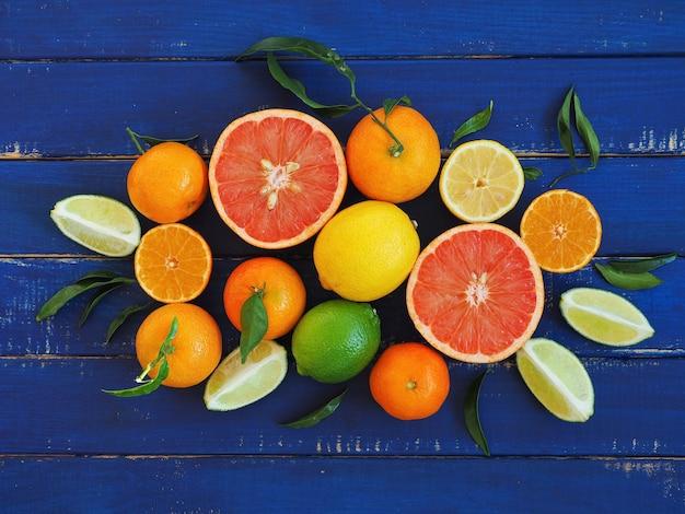 青い木の表面に柑橘系の果物の盛り合わせ-オレンジ、レモン、ライム、マンダリン、グレープフルーツ