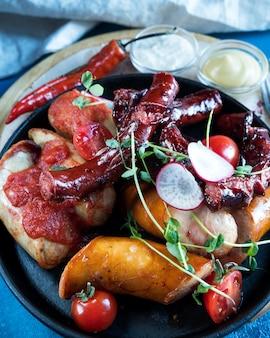Ассорти из жареных колбас на сковороде